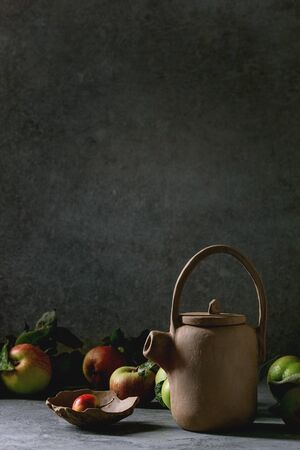 Hand made japanese style clay teapot with bowl and garden apples on table with dark background. Фото со стока - 128575897