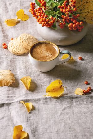 Cup of espresso coffee standing on linen table cloth with yellow autumn leaves, berries in ceramic vase and shortbread cookies with dark wall at background. Fall concept. Copy space