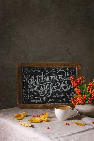 Cup of espresso coffee and vintage chalkboard handwritten lettering on linen table cloth with yellow autumn leaves and berries in ceramic vase. Dark wall at background. Fall concept, space