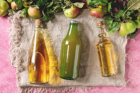 Variété de boissons aux pommes. Bouteilles de jus de pomme, vinaigre et cidre sur toile de lin avec pommes de jardin avec feuilles et branches sur fond de texture rose. Mise à plat, espace. Récolte d'automne à la maison.