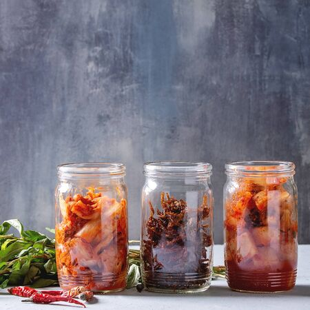 Korean traditional fermented appetizer kimchi cabbage and radish salad, hot spicy anchovies fish snack served in glass jars with Vietnamese oregano greens and chili peppers over grey blue table. Squar 스톡 콘텐츠