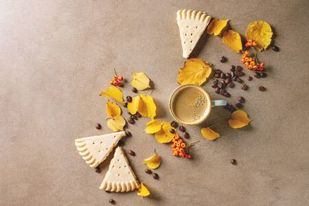 Cup of espresso coffee with yellow autumn leaves, berries, coffee beans and shortbread cookies over brown texture background. Fall concept. Flat lay, space Imagens