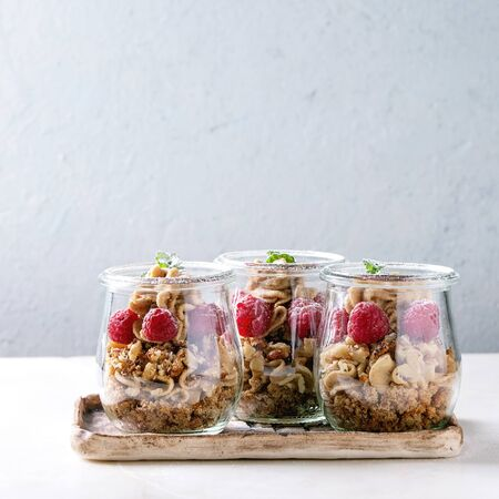 Layered dessert in jars. Biscuit, coffee cream, nuts, raspberries, fresh mint. Served on ceramic tray over white marble table. Square image