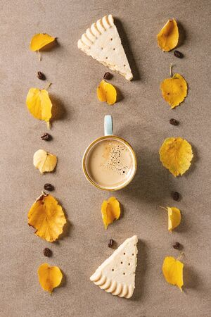Cup of espresso coffee with yellow autumn leaves, coffee beans and shortbread cookies over brown texture background. Fall concept. Flat lay, space Imagens