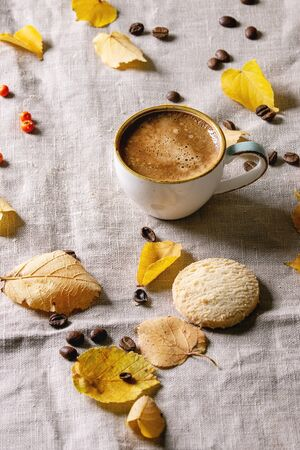 Cup of espresso coffee standing on linen table cloth with yellow autumn leaves, berries, coffee beans and shortbread cookies with dark wall at background. Fall concept. Copy space Imagens