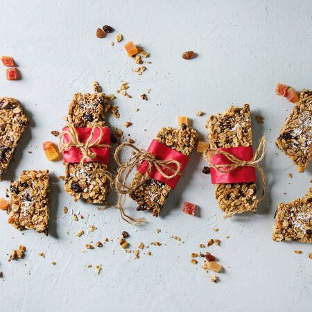 Homemade energy oats granola bars with dried fruits and nuts whole and broken wrapped in red paper over white texture background. Healthy snack. Flat lay, space. Square image