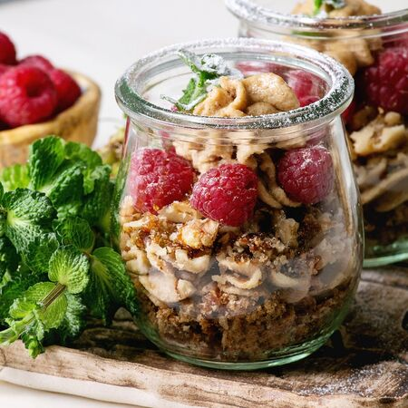 Layered dessert in jars. Biscuit, coffee cream, nuts, raspberries, fresh mint. Served on ceramic tray with berries and greens over white marble table. Square image