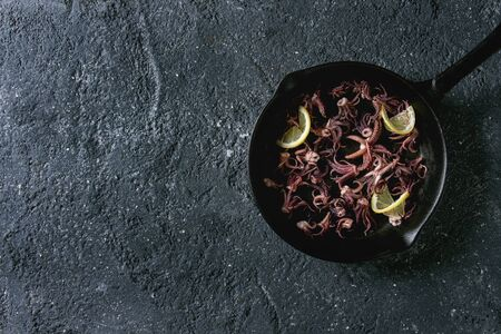 Grilled squids calamari tentacles with lemon in cast iron pan over black concrete background. Flat lay, space