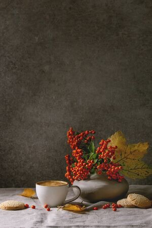 Cup of espresso coffee standing on linen table cloth with yellow autumn leaves, berries in ceramic vase, coffee beans and shortbread cookies with dark wall at background. Fall concept. Copy space