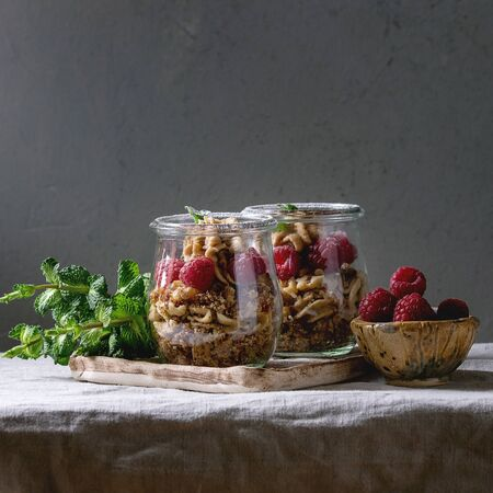Layered dessert in jars. Biscuit, coffee cream, nuts, raspberries, fresh mint. Served on ceramic tray with berries and greens over grey linen table cloth. Square image Imagens
