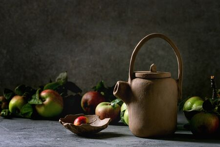 Hand made japanese style clay teapot with bowl and garden apples on table with dark background. Фото со стока