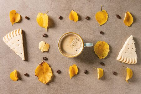 Cup of espresso coffee with yellow autumn leaves, coffee beans and shortbread cookies over brown texture background. Fall concept. Flat lay, space 写真素材
