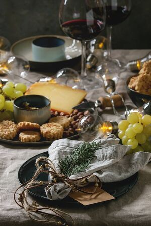 Home Christmas or New year dinner table set with wine, cheese plate, appetizers, lightning garland, xmas decoration and empty plate with cloth napkin. Stok Fotoğraf