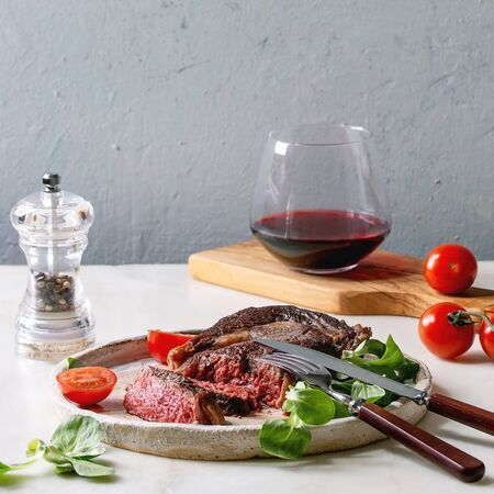 Grilled roasted sliced medium rare beef steak served in ceramic plate with green field salad, cherry tomatoes, cutlery, pepper, glass of red wine over white marble table.