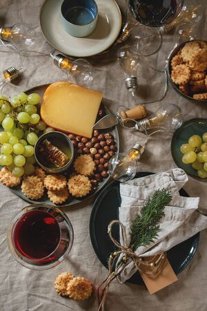 Home Christmas or New year dinner table set with wine, cheese plate, appetizers, lightning garland, xmas decoration and empty plate with cloth napkin. Flat lay