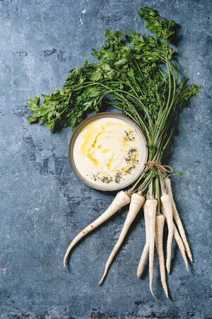 Parsnip cream soup in ceramic bowl with butter sauce, bundle of fresh parsnip and herbs over blue texture background. Flat lay, space Stockfoto