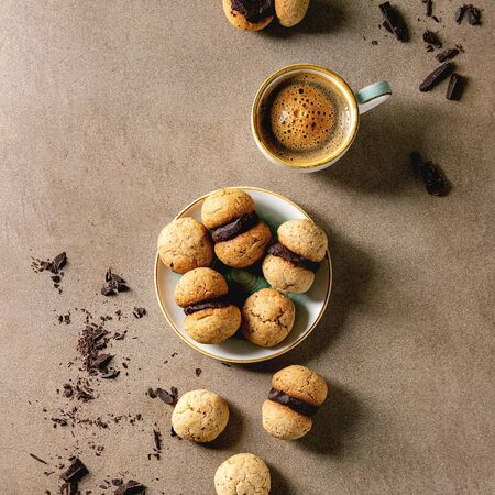 Baci di dama homemade italian hazelnut biscuits cookies with chocolate cream served in ceramic plate with cup of espresso coffee over brown texture background. Flat lay, space Фото со стока