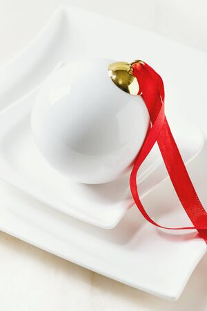 White porcelain Christmas ball with red ribbon in ceramic plate over white marble background. Close up. Modern Christmas concept.