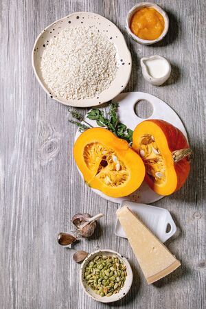Ingredients for cooking pumpkin risotto. Raw uncooked risotto rice in ceramic bowl, sliced pumpkin, cream, seeds, parmesan cheese, garlic and herbs over grey wooden background. Flat lay, space