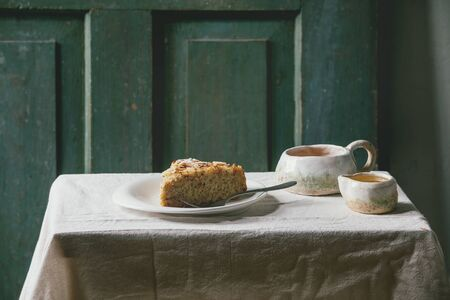 Piece of gluten free almond rosemary homemade cake decorated by almond and sugar powder on plate, with cup of tea, syrup and fork on linen table cloth with wooden door at background. Rustic style.
