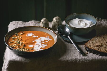 Pumpkin soup with cream and seeds in ceramic bowl, served with sour cream, rye bread, salt and pepper on grey linen tablecloth. Dark rustic style