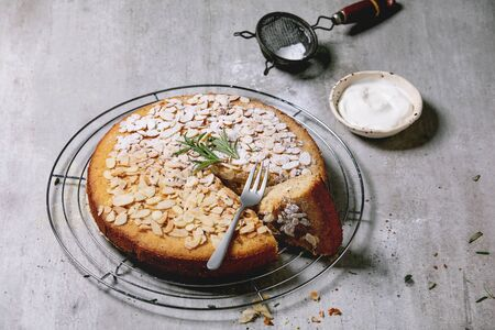 Gluten free almond rosemary homemade cake decorated by almond and sugar powder on cooling rack, serving with sour cream, fork and vintage sieve over grey texture background. Фото со стока