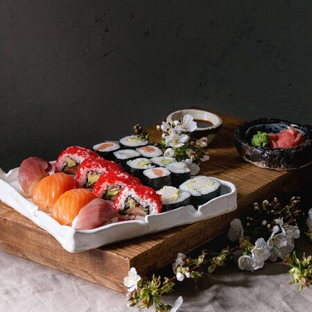 Sushi Set nigiri and sushi rolls on japanese wooden serving board with soy sauce, chopsticks, spring blossom cherry branches on grey linen table cloth. Japan menu
