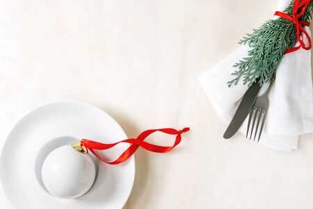 White porcelain Christmas ball with red ribbon in ceramic plate with fork, knife, napkin and thuja branch over white marble background. Flat lay, space. Modern Christmas concept.