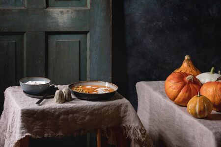 Pumpkin soup with cream and seeds in ceramic bowl, served with sour cream, rye bread, uncooked pumpkins on grey linen tablecloth. Dark rustic style