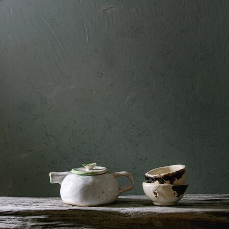 Craft handmade ceramic teapot and cup for tea ceremony standing on old wooden shelf in dark room. Фото со стока - 130065565