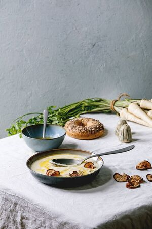 Parsnip cream soup in ceramic bowl with butter sauce, sun dried pears, bundle of fresh parsnip, bagel bread and herbs on kitchen table with white tablecloth Stockfoto