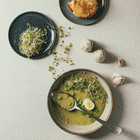 Started eaten green vegetable soup asparagus, broccoli or pea, decorated by green pea, sprouts and quail eggs in ceramic bowls with bread, salt and pepper over grey spotted background. Flat lay, space