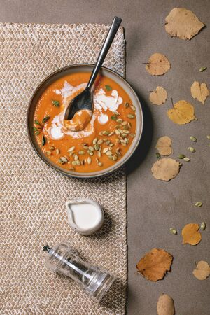 Pumpkin soup with cream and seeds in ceramic bowl, served with pepper mill and autumn leaves over brown texture background. Flat lay, space Stockfoto