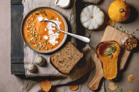 Pumpkin soup with cream and seeds in ceramic bowl on linen cloth, served with rye bread, baked and uncooked pumpkins and garlic, autumn leaves over brown texture background. Flat lay, space