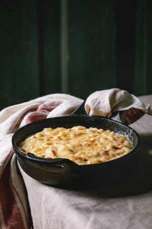 Classic american dish baked mac and cheese in cast iron pan with towel on kitchen table with linen tablecloth. Dark rustik style 写真素材
