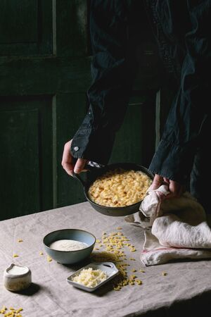 Young man in black holding classic american dish baked mac and cheese in cast iron pan with kitchen towel and ingredients above on kitchen table with linen tablecloth. Dark rustic style