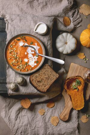 Pumpkin soup with cream and seeds in ceramic bowl on linen cloth, served with rye bread, baked and uncooked pumpkins, autumn leaves over brown texture background. Flat lay, space 写真素材