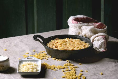 Classic american dish baked mac and cheese in cast iron pan with kitchen towel and ingredients above on kitchen table with linen tablecloth. Dark rustic style