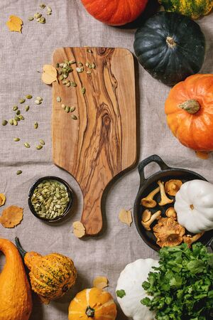 Variety of colorful pumpkins, edible and decorative, with autumn leaves, oregano greens, chanterelles mushrooms, pumpkin seeds and empty wooden cutting board over grey linen cloth. Flat lay, space