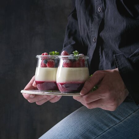 Woman in black shirt holding in hands homemade classic dessert Panna cotta with raspberry and blueberry berries and jelly in jars, decorated by mint and sugar powder. Dark background. 스톡 콘텐츠