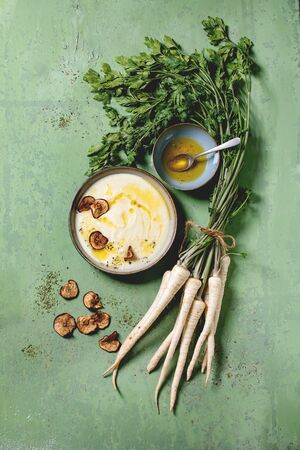 Parsnip cream soup in ceramic bowl with sun dried pears, butter sauce, bundle of fresh parsnip and herbs over green texture background. Flat lay, space Stockfoto