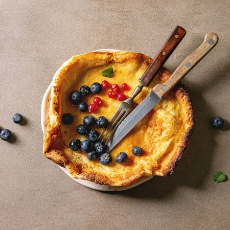 Fresh baked Dutch baby pancake in ceramic plate served with blackberry and red currant berries, bowl of honey, vintage cutlery over beige background. Flat lay, space Фото со стока
