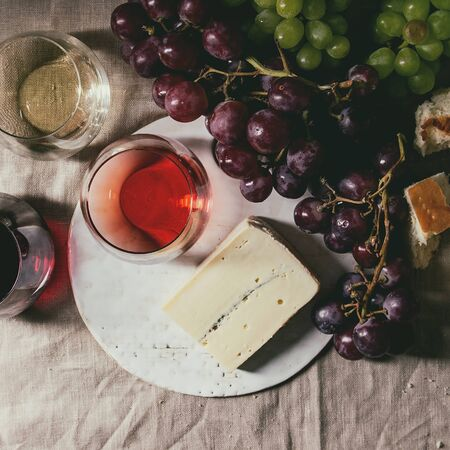 Variety of wine. Red, rose and white wine in old fashion glasses with bunches of grapes, blue cheese on ceramic board and bread on grey linen cloth. Dark still life. Flat lay, space