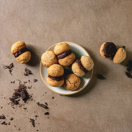 Baci di dama homemade italian hazelnut biscuits cookies with chocolate cream served in ceramic plate over brown texture background. Flat lay, copy space