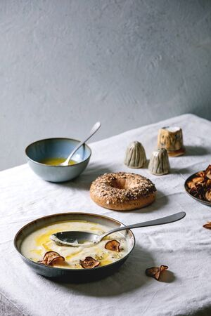Parsnip or cauliflower cream soup in ceramic bowl with butter sauce, sun dried pears, bagel bread and herbs on kitchen table with white tablecloth