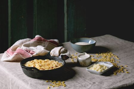 Classic american dish baked mac and cheese in cast iron pan with kitchen towel and ingredients above on kitchen table with linen tablecloth. Dark rustik style