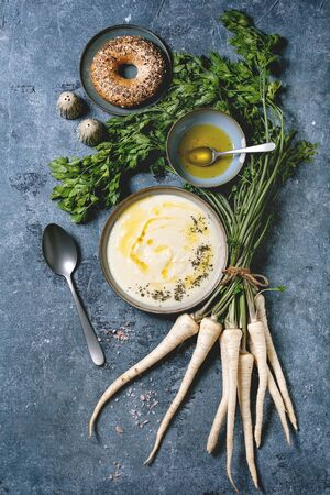 Parsnip cream soup in ceramic bowl with butter sauce, bagel bread, bundle of fresh parsnip and herbs over blue texture background. Flat lay, space Stockfoto
