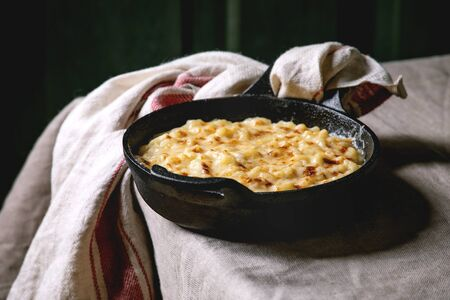 Classic american dish baked mac and cheese in cast iron pan with towel on kitchen table with linen tablecloth. Dark rustik style Imagens