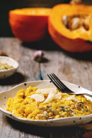 Traditional vegetarian pumpkin risotto italian dish in ceramic plate on old wooden kitchen table with ingredients above. Rustic style Imagens