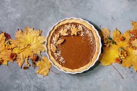 Traditional homemade autumn pumpkin pie for Thanksgiving or Halloween dinner served in ceramic dish with yellow autumn leaves over grey texture background. Flat lay, space